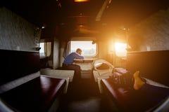 Ένα άτομο κάθεται σε ένα τραίνο κοντά στο παράθυρο Στοκ Φωτογραφίες