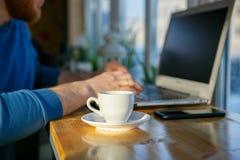 Ένα άτομο κάθεται σε ένα lap-top δίπλα σε ένα φλιτζάνι του καφέ Στοκ φωτογραφία με δικαίωμα ελεύθερης χρήσης