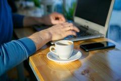 Ένα άτομο κάθεται σε ένα lap-top δίπλα σε ένα φλιτζάνι του καφέ Στοκ Εικόνες