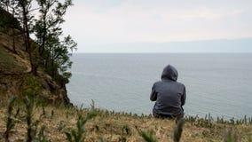 Ένα άτομο κάθεται στην ακτή στο νεφελώδη καιρό και συλλογίζεται 4k, χρονικό σφάλμα απόθεμα βίντεο