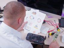 Ένα άτομο κάθεται στο γραφείο με μια γραφικά κάρτα, χρήματα και ένα πρόγραμμα Στοκ Εικόνες