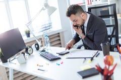 Ένα άτομο κάθεται στο γραφείο στο γραφείο, μιλά στο τηλέφωνο, κρατά έναν δείκτη στο χέρι του και βασίζεται στο α Στοκ εικόνα με δικαίωμα ελεύθερης χρήσης