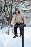 Ένα άτομο κάθεται στο γυμναστικό χειμώνα φραγμών στοκ φωτογραφία