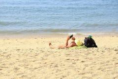 Ένα άτομο κάνει ηλιοθεραπεία στην παραλία και αγγίζει τον κινητό, Pattaya Ταϊλάνδη Στοκ Εικόνα