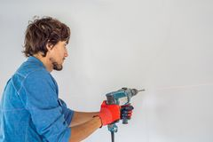 Ένα άτομο κάνει μια τρύπα στον τοίχο με ένα τρυπάνι στοκ φωτογραφίες με δικαίωμα ελεύθερης χρήσης