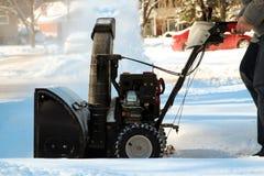 Ένα άτομο καθαρίζει το χιόνι από τα πεζοδρόμια με snowblower Στοκ φωτογραφία με δικαίωμα ελεύθερης χρήσης