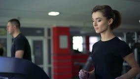 Ένα άτομο και ένα κορίτσι που τρέχουν treadmill στη γυμναστική φιλμ μικρού μήκους