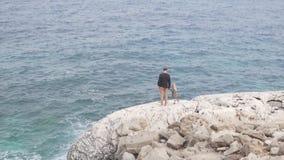 Ένα άτομο και η μικρή κόρη του στέκονται σε έναν άσπρο βράχο και εξετάζουν τον ωκεανό απόθεμα βίντεο