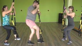 Ένα άτομο και ένα κορίτσι είναι δεσμευμένα στους βρόχους του TRX εκτελώντας τη βουλγαρική διάσπαση-στάση οκλαδόν ασκήσεων, ενίσχυ απόθεμα βίντεο