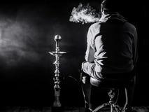 ένα άτομο καπνίζει ένα hookah σε ένα μαύρο υπόβαθρο, όμορφος φωτισμός στοκ εικόνες
