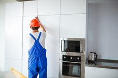 Ένα άτομο κατασκευής, σε ομοιόμορφο και ένα κράνος, θέτει την πόρτα στο ντουλάπι κουζινών στοκ εικόνα με δικαίωμα ελεύθερης χρήσης