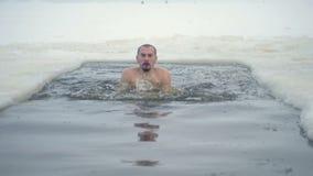 Ένα άτομο κολυμπά σε μια τρύπα πάγου και προσπαθεί να πάρει τις βαθιά εισπνοές απόθεμα βίντεο