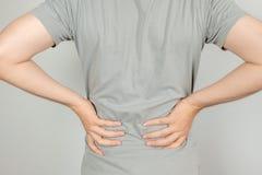 Ένα άτομο κράτησε το χέρι της πίσω από τον με τον πόνο στην πλάτη Έννοια υγειονομικής περίθαλψης στοκ εικόνες