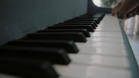 Ένα άτομο κρατά ένα δάχτυλο στα κλειδιά του πιάνου Χέρια του αρσενικού παιχνιδιού μουσικών στο πιάνο Κλείστε επάνω τα δάχτυλα του απόθεμα βίντεο