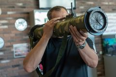 Ένα άτομο κρατά στα χέρια του μια χειροβομβίδα επιθέσεων εκτοξευτών ρουκετών ενάντια σε έναν καφετή τουβλότοιχο στοκ εικόνα