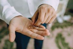 Ένα άτομο κρατά στα χέρια του στις παλάμες των γαμήλιων χρυσών δαχτυλιδιών Κινηματογράφηση σε πρώτο πλάνο Στοκ φωτογραφία με δικαίωμα ελεύθερης χρήσης