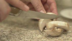 Ένα άτομο κόβει τα μανιτάρια στην κουζίνα απόθεμα βίντεο