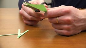 Ένα άτομο κόβει τις λουρίδες της Πράσινης Βίβλου φιλμ μικρού μήκους