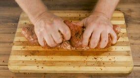 Ένα άτομο μαγειρεύει το κρέας σε έναν τέμνοντα πίνακα στον πίνακα από τις παλαιές ξύλινες σανίδες Τα αρσενικά χέρια ψεκάζουν τα κ απόθεμα βίντεο