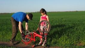 Ένα άτομο με ένα παιδί επισκευάζει ένα ποδήλατο Μπαμπάς με μια κόρη με ένα ποδήλατο στη φύση Το άτομο επισκευάζει το ποδήλατο απόθεμα βίντεο