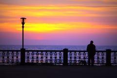 Ένα άτομο με ένα σκυλί στην αυγή Στοκ φωτογραφία με δικαίωμα ελεύθερης χρήσης