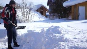 Ένα άτομο με ένα φτυάρι στο χέρι του για να καθαρίσει την πορεία από το χιόνι κοντά στο σπίτι HD, 1920x1080 κίνηση αργή φιλμ μικρού μήκους