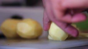 Ένα άτομο με ένα μαχαίρι στον πίνακα κόβει τις πατάτες απόθεμα βίντεο