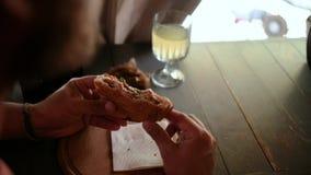 ένα άτομο με μια γενειάδα και μια ΚΑΠ κρατά ένα σάντουιτς στα χέρια του, και τον δαγκώνει έπειτα καθμένος σε έναν καφέ E 4K 4k VI απόθεμα βίντεο