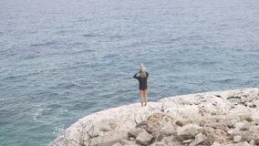 Ένα άτομο με μια μικρή κόρη κατέβηκε σε έναν υψηλό απότομο βράχο στη θάλασσα απόθεμα βίντεο