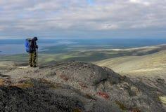 Ένα άτομο με ένα μπλε σακίδιο πλάτης από την πλάτη στα βουνά στοκ εικόνα