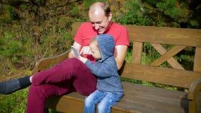 Ένα άτομο με ένα παιδί που χρησιμοποιεί μια συνεδρίαση smartphone σε έναν πάγκο Χαμόγελο πατέρων και γιων που εξετάζει την οθόνη  φιλμ μικρού μήκους