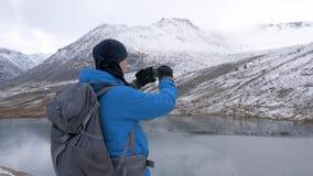Ένα άτομο με ένα σακίδιο πλάτης ταξιδεύει στα βουνά Γύρω από τον είναι όμορφα βουνά και μια σαφής λίμνη Φωτογραφίζει απόθεμα βίντεο