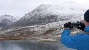 Ένα άτομο με ένα σακίδιο πλάτης ταξιδεύει στα βουνά Γύρω από τον είναι όμορφα βουνά και μια σαφής λίμνη Φωτογραφίζει φιλμ μικρού μήκους