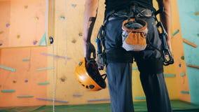 Ένα άτομο με την αναρρίχηση του εξοπλισμού στέκεται κοντά σε έναν τοίχο, κλείνει επάνω απόθεμα βίντεο