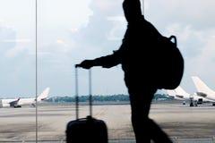 Ένα άτομο με τις αποσκευές εξετάζει τα αεροπλάνα μέσω του γυαλιού της αναμονής Στοκ εικόνα με δικαίωμα ελεύθερης χρήσης