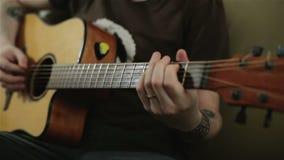 Ένα άτομο με τις δερματοστιξίες που παίζει την κιθάρα φιλμ μικρού μήκους