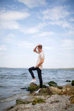 Ένα άτομο με το σύγχρονο hairstyle στα περιστασιακά ενδύματα στις πέτρες σε μια παραλία ποταμών Μια νέα αρσενική τοποθέτηση σε έν Στοκ εικόνες με δικαίωμα ελεύθερης χρήσης