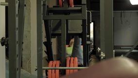 Ένα άτομο με το υπερβολικό βάρος που κάνει τους Τύπους ποδιών στον προσομοιωτή στη γυμναστική Κατάρτιση ικανότητας r φιλμ μικρού μήκους