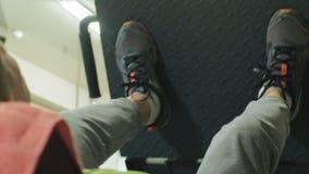 Ένα άτομο με το υπερβολικό βάρος που κάνει τους Τύπους ποδιών στον προσομοιωτή στη γυμναστική Κατάρτιση ικανότητας r απόθεμα βίντεο