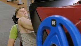 Ένα άτομο με το υπερβολικό βάρος που κάνει τους Τύπους ποδιών στον προσομοιωτή στη γυμναστική r r φιλμ μικρού μήκους