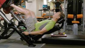 Ένα άτομο με το υπερβολικό βάρος που κάνει τους Τύπους ποδιών στον προσομοιωτή στη γυμναστική r r απόθεμα βίντεο