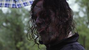 Ένα άτομο με το makeup ενός zombie στέκεται με ένα τηλέφωνο απόθεμα βίντεο