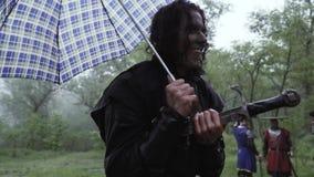 Ένα άτομο με το zombie makeup περπατά με ένα ξίφος στο σώμα του απόθεμα βίντεο