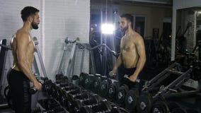 Ένα άτομο μιας φίλαθλης διάπλασης εκπαιδεύει τους μυς και των δύο χεριών χρησιμοποιώντας έναν αλτήρα στην αθλητική αίθουσα μπροστ απόθεμα βίντεο