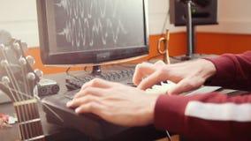 Ένα άτομο μουσικών που παίζει σε ένα Midi-πληκτρολόγιο στο στούντιο υγιούς καταγραφής απόθεμα βίντεο