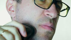 Ένα άτομο ξυρίζει το μάγουλό του με ένα ηλεκτρικό ξυράφι, ένα κακό ξυράφι απόθεμα βίντεο