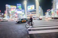 Ένα άτομο οδηγά ένα ποδήλατο που περνά το δρόμο με έντονη κίνηση του περάσματος Shibuya στοκ εικόνες με δικαίωμα ελεύθερης χρήσης