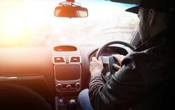 Ένα άτομο οδηγεί ένα αυτοκίνητο Ο οδηγός οδηγεί με το αυτοκίνητο κατά μήκος του δρόμου Στοκ Φωτογραφίες