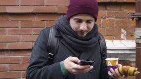 Ένα άτομο πίνει τον καφέ και το smartphone χρήσης στεμένος κοντά σε ένα σπίτι στην αλέα απόθεμα βίντεο