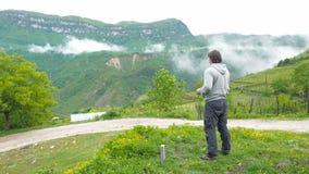 Ένα άτομο πίνει το τσάι στα βουνά απόθεμα βίντεο